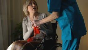 Νοσοκόμα που παίρνει μαζί τις βελόνες από τη γυναίκα με την ασθένεια Parkinsons που προσπαθεί να πλέξει απόθεμα βίντεο