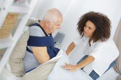 Νοσοκόμα που παίρνει την προσοχή που υφίσταται τον ανώτερο ασθενή στο σπίτι στοκ φωτογραφία με δικαίωμα ελεύθερης χρήσης
