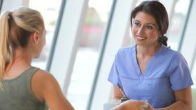 Νοσοκόμα που παίρνει τον εφηβικό θηλυκό ασθενή Froom σημειώσεων απόθεμα βίντεο