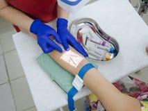 Νοσοκόμα που παίρνει το αίμα για την ανάλυση μέσω της συσκευής προβολέων φλεβών στοκ εικόνες