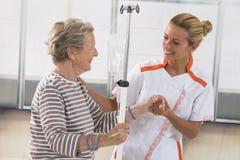 Νοσοκόμα που περπατά δίπλα σε έναν ασθενή με IV σταλαγματιά Στοκ φωτογραφίες με δικαίωμα ελεύθερης χρήσης