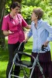 Νοσοκόμα που περπατά με μια γυναίκα με έναν περιπατητή Στοκ Εικόνες