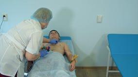 Νοσοκόμα που προετοιμάζει το υπομονετικό στήθος ` s για να συνδέσει τα μαξιλάρια ηλεκτροδίων για ECG Στοκ Εικόνες