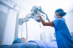 Νοσοκόμα που ρυθμίζει την των ακτίνων X μηχανή πέρα από τον ασθενή στοκ φωτογραφίες