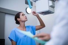 Νοσοκόμα που ρυθμίζει την των ακτίνων X μηχανή στοκ εικόνα