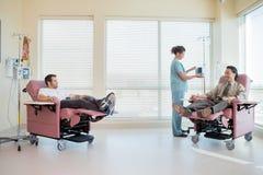 Νοσοκόμα που ρυθμίζει IV μηχανή ενώ ασθενείς Στοκ εικόνες με δικαίωμα ελεύθερης χρήσης