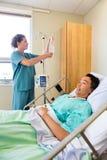 Νοσοκόμα που ρυθμίζει IV σταλαγματιά στη ράβδο με τον ασθενή επάνω Στοκ Φωτογραφία