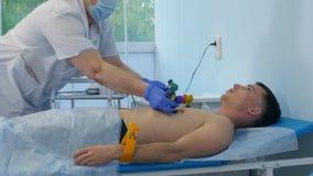 Νοσοκόμα που συνδέει τα μαξιλάρια ηλεκτροδίων ECG με το αρσενικό υπομονετικό στήθος ` s Στοκ Εικόνες