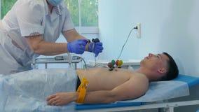 Νοσοκόμα που συνδέει τα μαξιλάρια ηλεκτροδίων ECG με το στήθος του αρσενικού ασθενή απόθεμα βίντεο