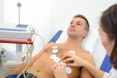 Νοσοκόμα που συνδέει τα μαξιλάρια οργάνων ελέγχου καρδιών με το ανθρώπινο στήθος στοκ φωτογραφία με δικαίωμα ελεύθερης χρήσης