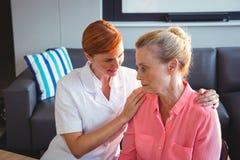 Νοσοκόμα που φροντίζει μια λυπημένη ανώτερη γυναίκα στοκ φωτογραφία