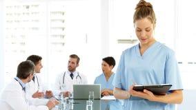Νοσοκόμα που χαμογελά στη κάμερα ενώ το προσωπικό μιλά πίσω από την φιλμ μικρού μήκους