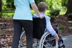 Νοσοκόμα που ωθεί την ηλικιωμένη γυναίκα στην αναπηρική καρέκλα Στοκ Εικόνες