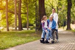 Νοσοκόμα που ωθεί το ανώτερο άτομο στην αναπηρική καρέκλα με την εγγονή του στοκ εικόνες