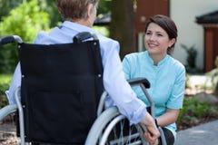 Νοσοκόμα στα χαμόγελα παλτών εργαστηρίων στη γυναίκα Στοκ Εικόνα