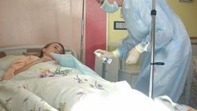Νοσοκόμα στη μάσκα και γάντια που προετοιμάζουν τους θηλυκούς ασθενείς για dropper απόθεμα βίντεο