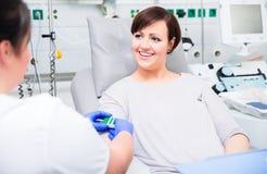 Νοσοκόμα στο νοσοκομείο που ελέγχει την πρόσβαση στο χορηγό αίματος γυναικών στοκ εικόνα