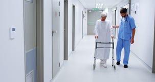 Νοσοκόμος που βοηθά τον ανώτερο ασθενή σε χρησιμοποίηση ενός πλαισίου περπατήματος φιλμ μικρού μήκους