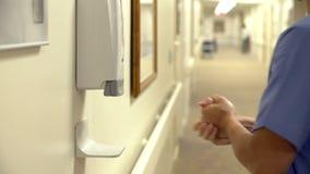 Νοσοκόμος που χρησιμοποιεί Sanitizer χεριών στο νοσοκομείο απόθεμα βίντεο