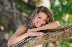 Νοσταλγικές στιγμές ενός όμορφου κοριτσιού όπως στηρίζεται σε έναν κορμό δέντρων στοκ εικόνα