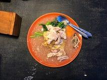 Νουντλς που ολοκληρώνονται με το χοιρινό κρέας και το λαχανικό στο πορτοκαλί πιάτο στο μαύρο πίνακα Στοκ Εικόνες