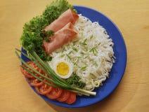 Νουντλς ρυζιού με το τεμαχισμένο μπέϊκον, ζαμπόν σε ένα μπλε πιάτο στοκ εικόνες με δικαίωμα ελεύθερης χρήσης