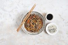 Νουντλς φαγόπυρου με τα λαχανικά και το κρέας που διακοσμούνται με το σουσάμι και φύκια στο κύπελλο στο γκρίζο υπόβαθρο r στοκ εικόνες