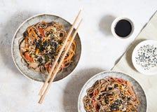 Νουντλς φαγόπυρου με τα λαχανικά και το κρέας που διακοσμούνται με το σουσάμι και φύκια στα κύπελλα στο γκρίζο υπόβαθρο r στοκ φωτογραφία με δικαίωμα ελεύθερης χρήσης