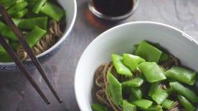 Νουντλς φαγόπυρου με τα πράσινα φασόλια στα κεραμικές κύπελλα και τη σάλτσα σόγιας απόθεμα βίντεο