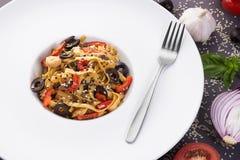 Νουντλς Wok αυγών με το μοσχαρίσιο κρέας και τα λαχανικά Διακοσμημένος με τα λαχανικά, το βασιλικό και τους σπόρους σουσαμιού στοκ εικόνα