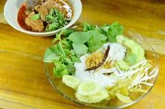 νουντλς ρυζιού και φρέσκο λαχανικό με το πικάντικο χοιρινό κρέας μπριζολών και την κόκκινη σάλτσα δέντρων βαμβακιού κόκκαλων Στοκ Εικόνες