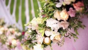 Ντεκόρ ανθοδεσμών τεχνητών λουλουδιών στη γαμήλια τελετή με το ελαφρύ υπόβαθρο θαμπάδων απόθεμα βίντεο