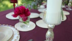 Ντεκόρ γαμήλιων πινάκων στη φύση με τα αναμμένα κεριά, κινηματογράφηση σε πρώτο πλάνο φιλμ μικρού μήκους