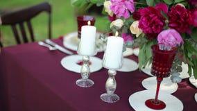 Ντεκόρ γαμήλιων πινάκων στη φύση με τα αναμμένα κεριά steadicam πυροβολισμός φιλμ μικρού μήκους