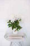 Ντεκόρ λουλουδιών, φρέσκα peonies στην καρέκλα σχεδιαστών στην άσπρη αίθουσα INT στοκ εικόνα