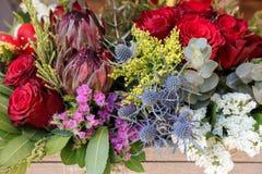 Ντεκόρ Πάσχας Εορταστική ρύθμιση λουλουδιών Protea, των κόκκινων τριαντάφυλλων, του sinuatum limonium, του eryngium, των φύλλων ε στοκ εικόνα