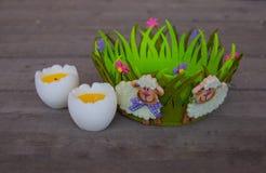 Ντεκόρ Πάσχας με τα baa-αρνιά στο πράσινα καλάθι και τα αυγά στοκ φωτογραφίες