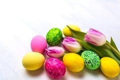 Ντεκόρ Πάσχας με τις τουλίπες και τα πράσινα, κίτρινα, ρόδινα αυγά στοκ φωτογραφία