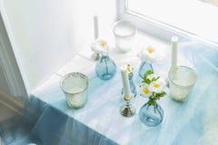 Ντεκόρ του photostudio - άσπρα κεριά, μπλε κλωστοϋφαντουργικό προϊόν Στοκ Εικόνα