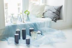 Ντεκόρ των γκρίζων κεριών photostudio, του λευκού και των μαξιλαριών, μπλε κλωστοϋφαντουργικό προϊόν Στοκ φωτογραφία με δικαίωμα ελεύθερης χρήσης