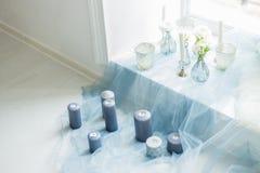 Ντεκόρ των γκρίζων κεριών photostudio, του λευκού και των μαξιλαριών, μπλε κλωστοϋφαντουργικό προϊόν Στοκ Εικόνες