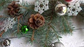 Ντεκόρ Χριστουγέννων, κώνοι πεύκων και παιχνίδια στο άσπρο υπόβαθρο νέες διακοπές έτους φιλμ μικρού μήκους