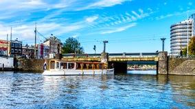 Ντεμοντέ βάρκα καναλιών που πηγαίνει κάτω από τη γέφυρα στο Stationsplein στον κεντρικό σταθμό στο κέντρο του Άμστερνταμ στοκ φωτογραφία με δικαίωμα ελεύθερης χρήσης