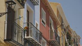Ντεμοντέ ευρωπαϊκά κατοικημένα κτήρια με τις πολύχρωμες προσόψεις Περιστροφή pinwheel σε ένα μπαλκόνι και πέταγμα απόθεμα βίντεο