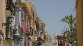 Ντεμοντέ νότια ευρωπαϊκά κατοικημένα κτήρια με τις πολύχρωμες προσόψεις Περιστροφή pinwheel σε ένα μπαλκόνι και φιλμ μικρού μήκους