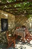 Ντεμοντέ πεζούλι καφέδων με τους πίνακες, τις καρέκλες και τα δέντρα στοκ φωτογραφίες
