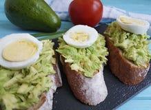Ντομάτα αβοκάντο αυγών σάντουιτς αγροτική στην μπλε ξύλινη γαστρονομία στοκ φωτογραφίες