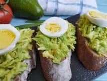Ντομάτα αβοκάντο αυγών σάντουιτς στην μπλε ξύλινη γαστρονομία στοκ φωτογραφία με δικαίωμα ελεύθερης χρήσης
