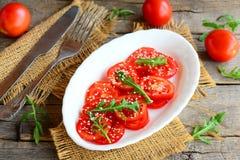 Ντομάτα, σαλάτα arugula Νόστιμη και σαλάτα διατροφής με τις ντομάτες, το arugula και τους σπόρους σουσαμιού σε ένα άσπρο πιάτο Δί Στοκ φωτογραφία με δικαίωμα ελεύθερης χρήσης