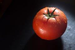 Ντομάτα στο μαύρο υπόβαθρο πλακών Στοκ Φωτογραφίες